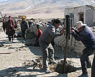 Labourers dig holes for fence posts around Lhasang's home to protect his family from potential brown bear attacks.