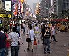 A man using his mobile phone stands in the crowd on Nanjing Road, a shopping street in Shanghai, China.
